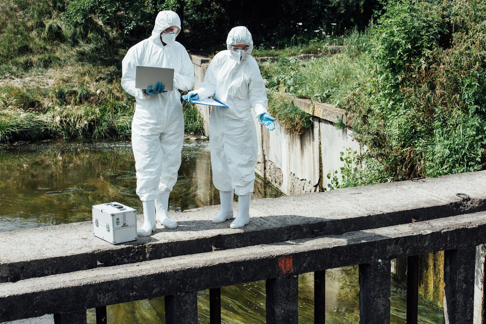 two sewage workers wearing protective masks and clothing checking water quality