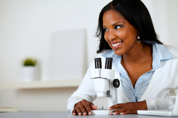 scientist studying and looking at a microscope