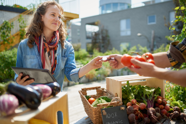 woman paying for organic tomatoes at farmers market